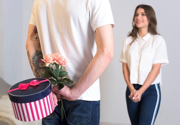 Mężczyzna trzyma prezent dla kobiety za plecami