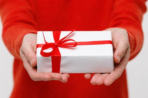 Mężczyzna trzyma prezent naprzód w jego ręce, zamyka up