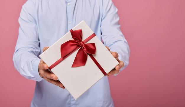Mężczyzna trzyma prezent w białym pudełku z niebieską pokrywką i białą kokardą