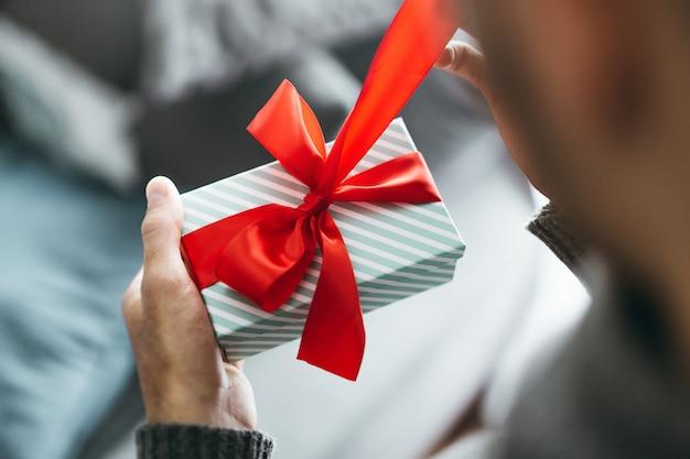 Mężczyzna trzyma prezent z czerwoną wstążką