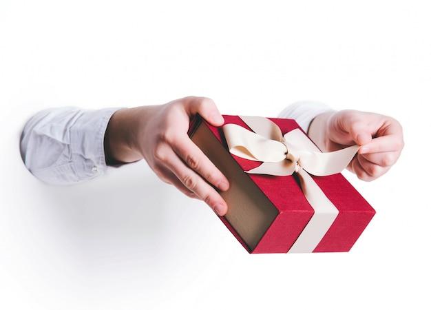Mężczyzna trzyma prezenta pudełko.
