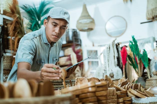Mężczyzna trzyma przedmiot rzemieślniczy i schowek, sprawdzając przedmioty wśród przedmiotów rzemiosła w galerii rzemiosła