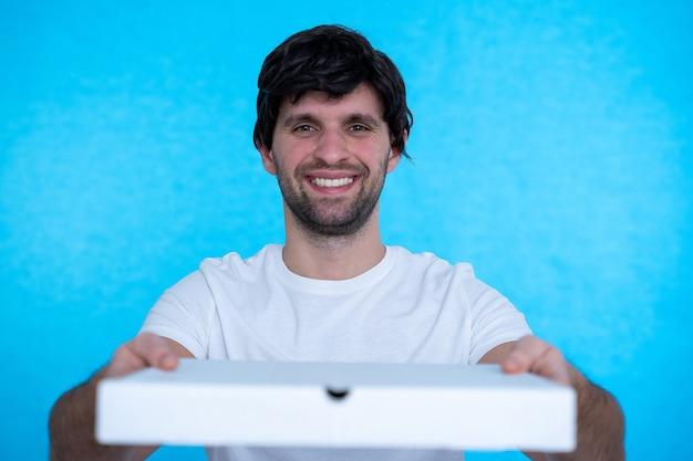Mężczyzna trzyma pudełka po pizzy na niebieskiej ścianie z zadowolonym wyrazem