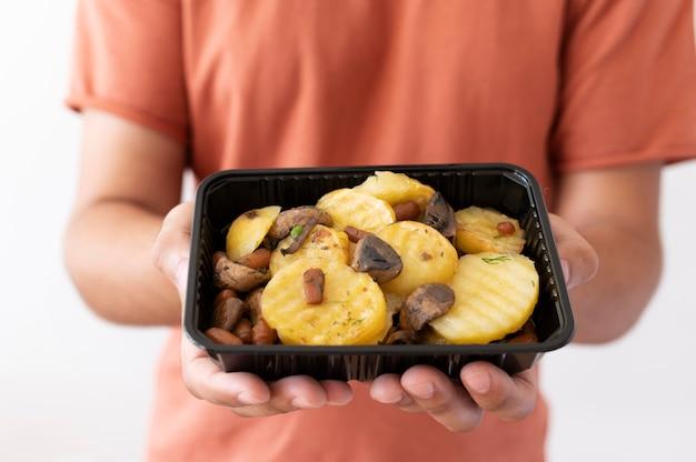 Mężczyzna trzyma pudełko darowanej żywności