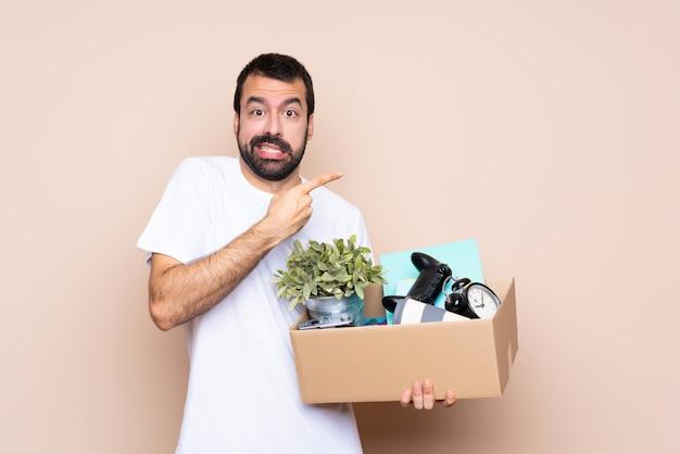 Mężczyzna trzyma pudełko i porusza się w nowym domu przestraszony i wskazując na bok
