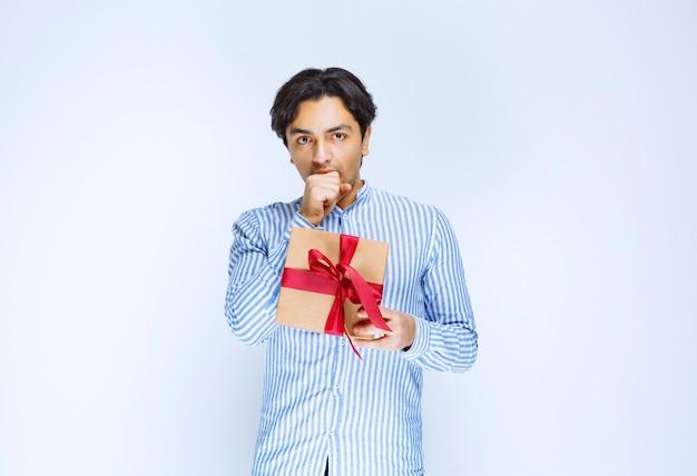 Mężczyzna trzyma pudełko kartonowe z czerwoną wstążką i kaszel o uwagę. zdjęcie wysokiej jakości