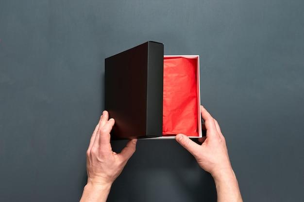 Mężczyzna trzyma pudełko z prezentem na szarym drewnianym stole.