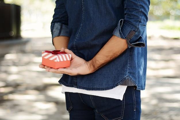 Mężczyzna trzyma pudełko za jego plecy.