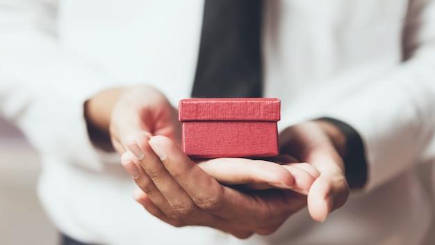 Mężczyzna trzyma pustego czerwonego prezenta pudełko. vintage ton.