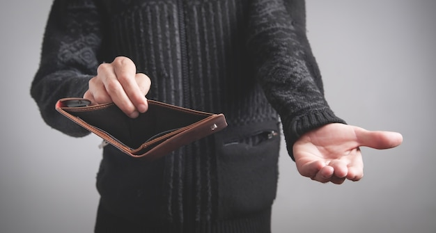 Mężczyzna trzyma pusty portfel. brak pieniędzy