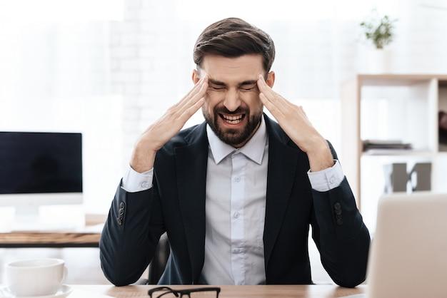 Mężczyzna trzyma ręce na głowie. czuje ból.