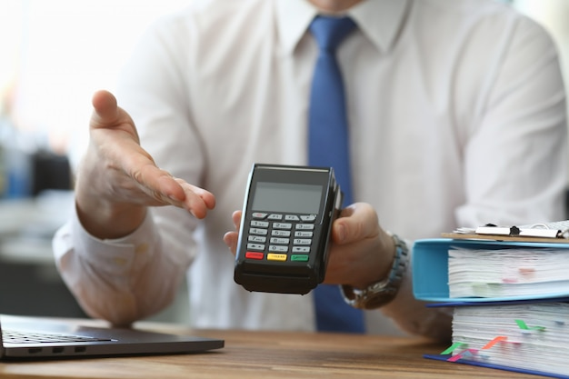 Mężczyzna trzyma rękę bezprzewodowy terminal do zapłaty