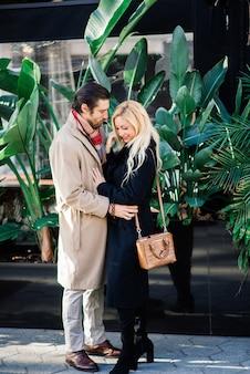 Mężczyzna trzyma rękę żony i czule na nią patrzy i spaceruje po ulicach miasta.
