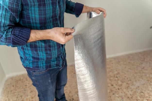 Mężczyzna trzyma rolkę tkaniny izolacyjnej, aby zainstalować laminowaną podłogę drewnianą