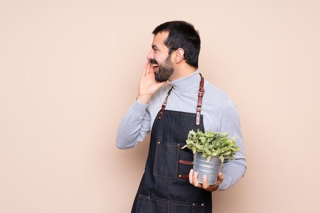 Mężczyzna trzyma rośliny krzyczy z szeroko otwartymi ustami do bocznego