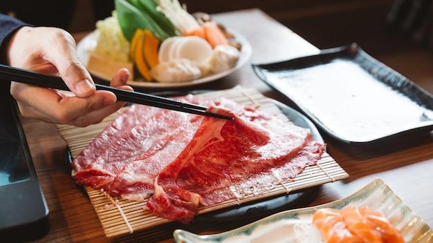 Mężczyzna trzyma rzadki plasterek wołowiny wagyu a5 pałeczkami do gotowania w gorącym garnku shabu.