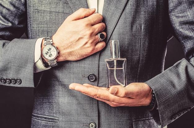 Mężczyzna trzyma się butelki perfum. oddaj się z zegarkiem na rękę w garniturze. butelka perfum lub wody kolońskiej i perfumy, kosmetyki, butelka wody kolońskiej zapach, mężczyzna gospodarstwa woda kolońska.