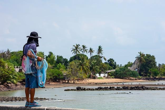 Mężczyzna trzyma sieci rybackie tło morze i niebo.