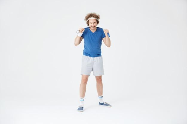Mężczyzna trzyma skakankę w ręce. wygląda agresywnie i zmotywowany