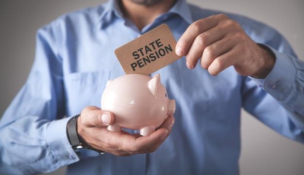 Mężczyzna trzyma skarbonkę emerytura państwowa