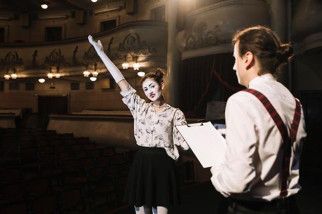Mężczyzna trzyma skrypty patrzeje żeńskiego mima spełniania na scenie