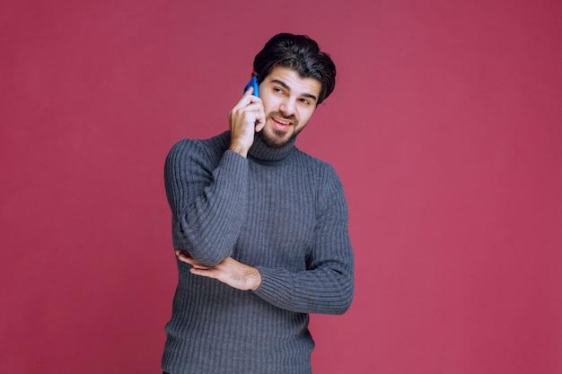 Mężczyzna trzyma smartfon do ucha i mówi.
