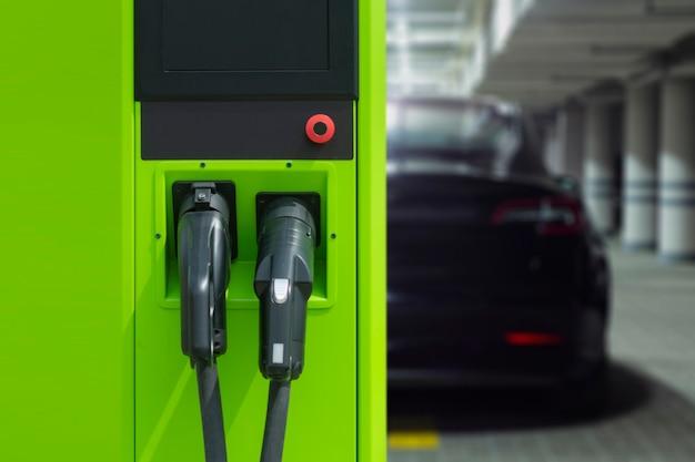 Mężczyzna trzyma smartfon z cyfrowym licznikiem paliwa na ekranie w tle stacji benzynowej i samochodu.