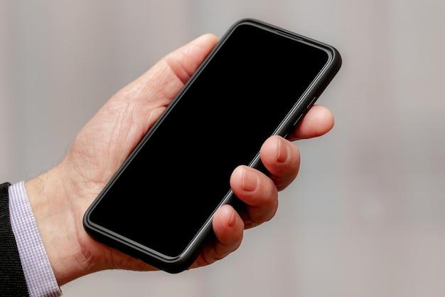 Mężczyzna trzyma smartfon z czarnym wyświetlaczem w ręku. skopiuj miejsce_