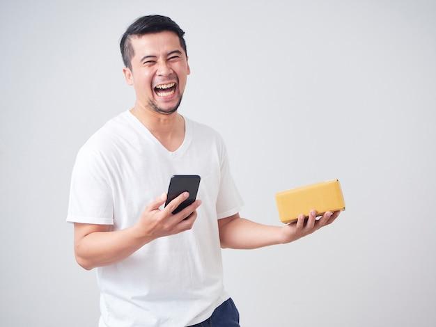 Mężczyzna trzyma smartphone i paczki