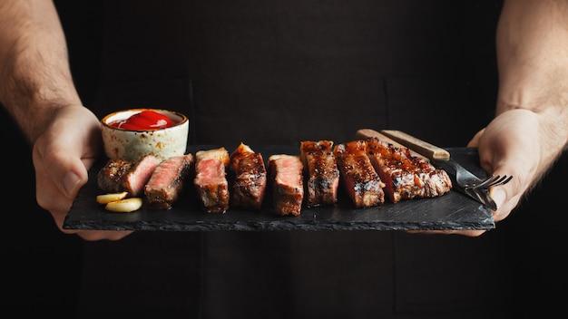 Mężczyzna trzyma soczystego piec na grillu wołowina stek.