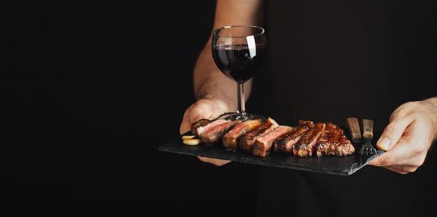 Mężczyzna trzyma soczysty piec na grillu wołowina stek.