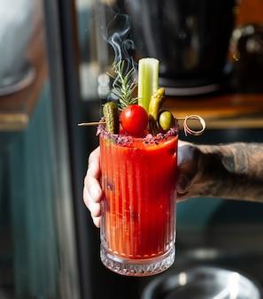 Mężczyzna trzyma sok pomidorowy przyozdobionym z selera kij oliwny marynowany pieprz ogórek