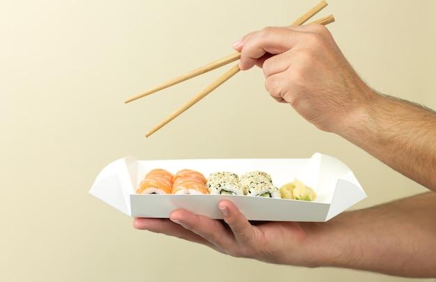 Mężczyzna trzyma sushi w jednorazowym talerzu i je japońskie jedzenie pałeczkami.