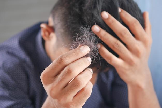 Mężczyzna trzyma swoją listę włosów z bliska