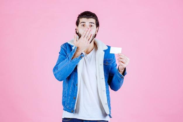 Mężczyzna trzyma swoją wizytówkę i wygląda na zdziwionego