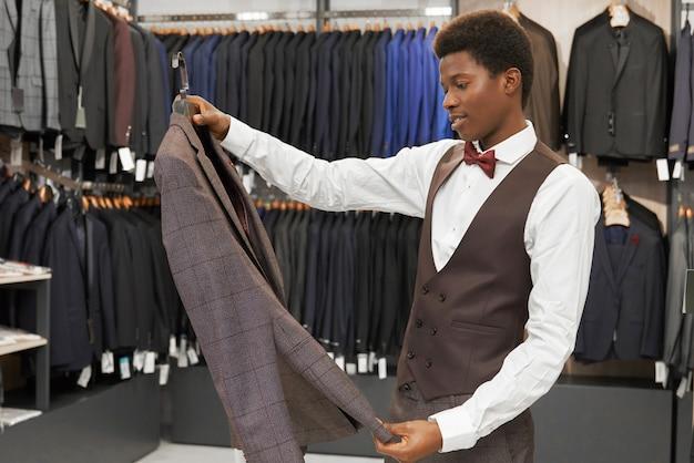 Mężczyzna trzyma szarą kurtkę na wieszaku, patrzeje, wybiera.