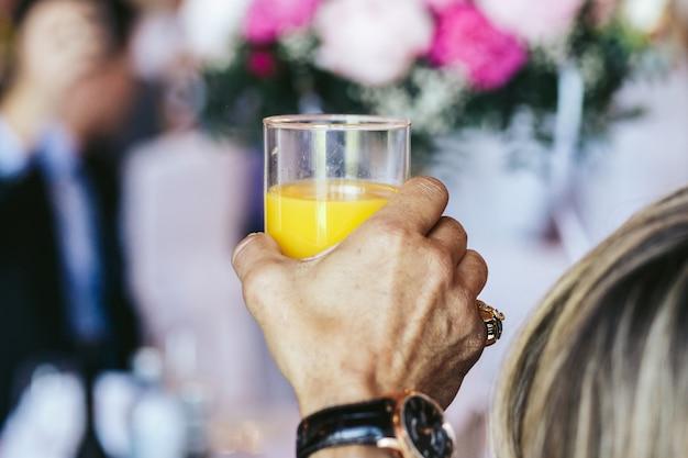 Mężczyzna trzyma szklankę soku pomarańczowego