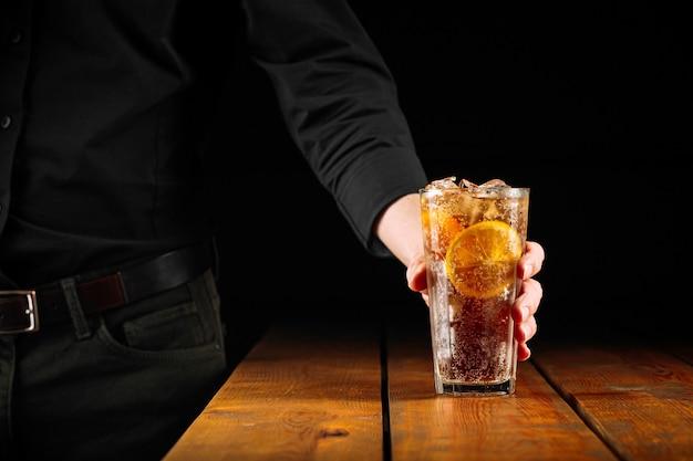 Mężczyzna trzyma szklankę świeżego koktajlu mrożonej herbaty long island
