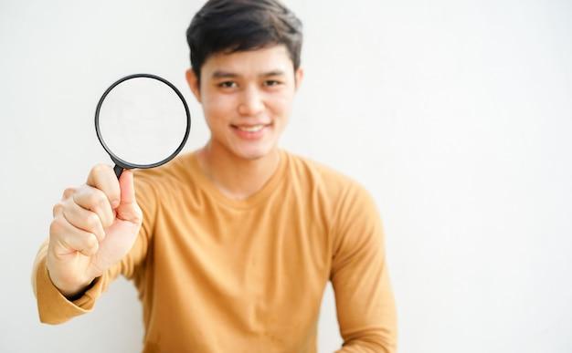 Mężczyzna trzyma szkło powiększające do wyszukiwania