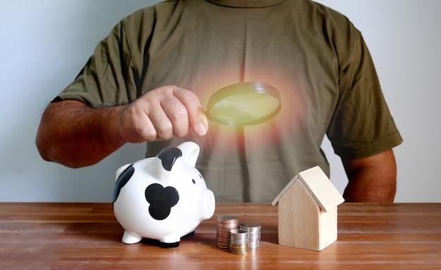 Mężczyzna trzyma szkło powiększające w ręku patrząc monety układania skarbonka drewniany domowy model na podłodze retrowood, koncepcja oszczędności