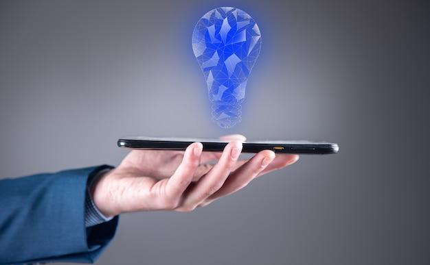 Mężczyzna trzyma tablet z grafiką żarówki