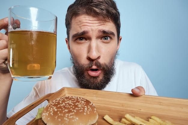 Mężczyzna trzyma tacę z fast foodami i piwem