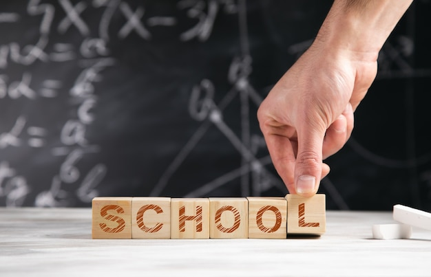 Mężczyzna trzyma tekst szkoły na drewnianych kostkach