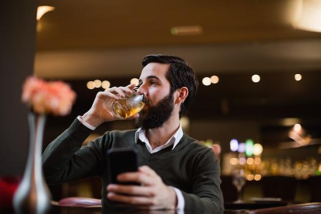 Mężczyzna trzyma telefon komórkowego i ma napój