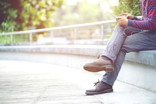 Mężczyzna trzyma telefon komórkowy siedzi w parku
