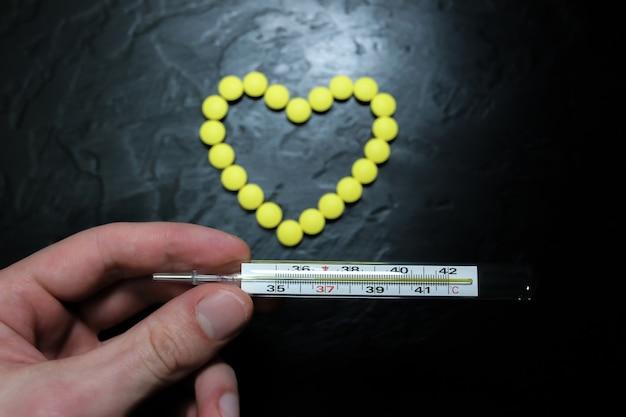 Mężczyzna trzyma termometr rtęciowy o temperaturze 36,6. zdrowa osoba. pigułki w formie serca na tle. zdrowy układ krążenia.