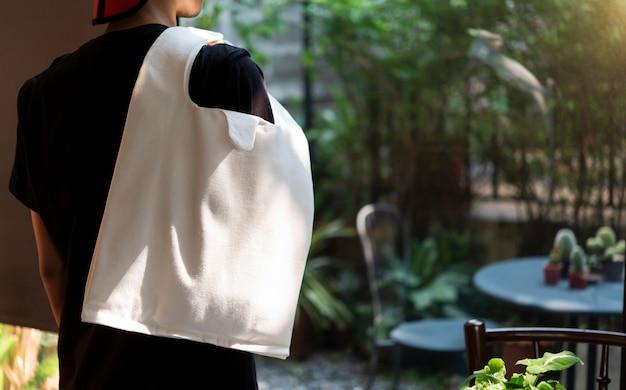 Mężczyzna trzyma torby brezentową tkaninę na restauracyjnym tle