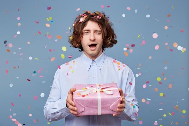 Mężczyzna trzyma udekorowany prezent w dużym pudełku