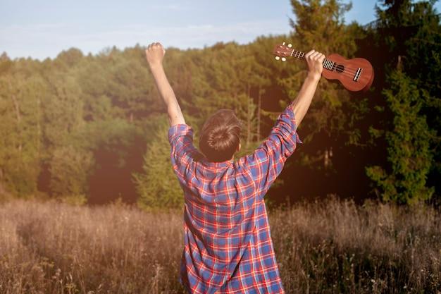 Mężczyzna trzyma ukulele w powietrzu