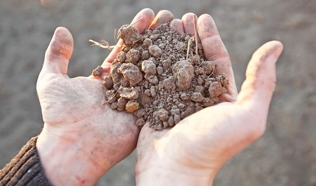 Mężczyzna trzyma w dłoni bardzo suchą glebę. pojęcie erozji gleby z powodu braku opadów z powodu globalnego ocieplenia